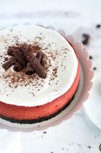 red velvet cheesecake on a white plate with chocolate curls