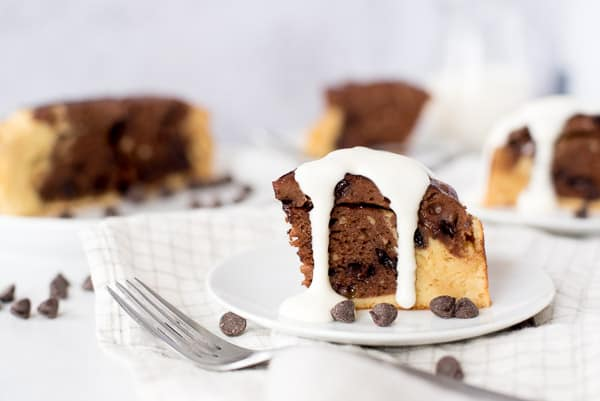 Slice of a chocolate swirl breakfast cake topped with yogurt on a white plate
