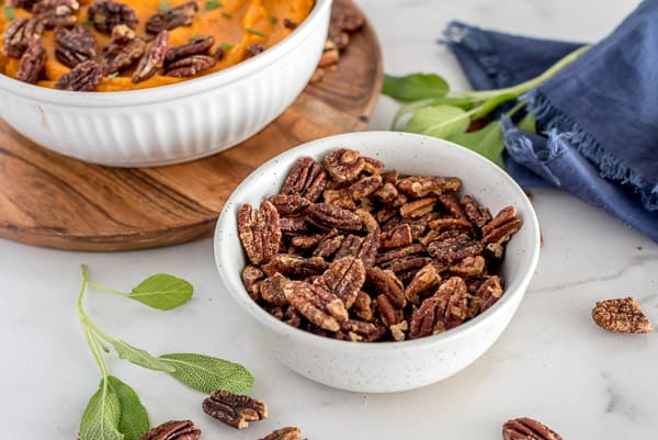 Roasted pecans in a white bowl with sweet potatoes in the background
