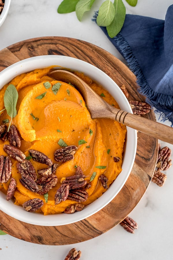 White bowl of mashed sweet potatoes with pecans on top