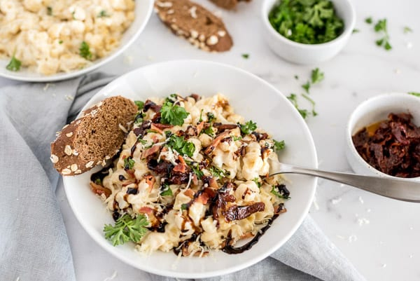 cauliflower mac and cheese in a white bowl topped with herbs