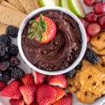 white bowl of chocolate hummus with a side of strawberries, blackberries, pretzels, apples, and graham crackers