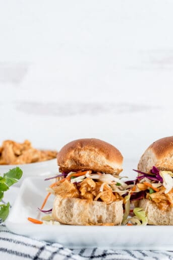 BBQ chicken on a bun topped with coleslaw on a white plate