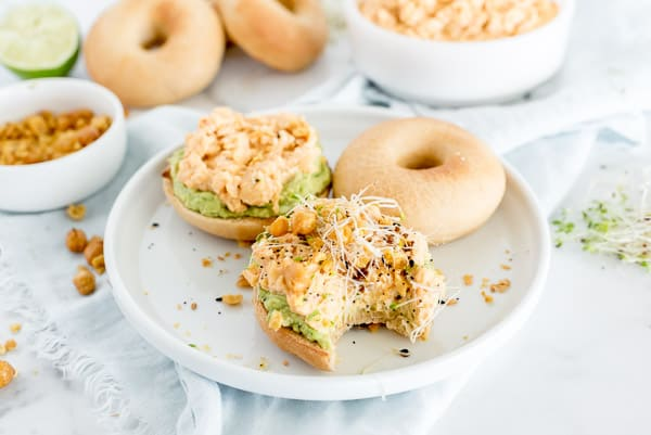 bagel with chickpea salad on it with sprouts and pepper.