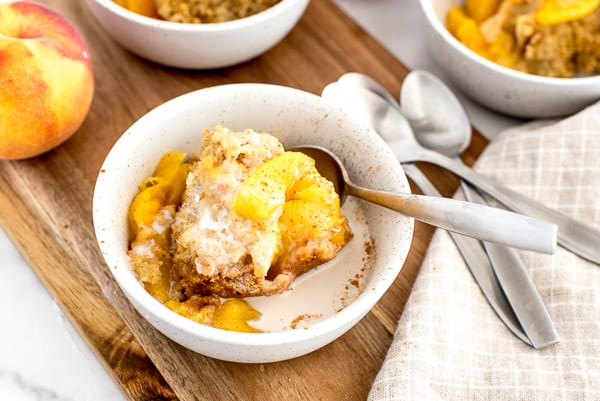 2 white bows with peach cobbler, cream, and a spoon