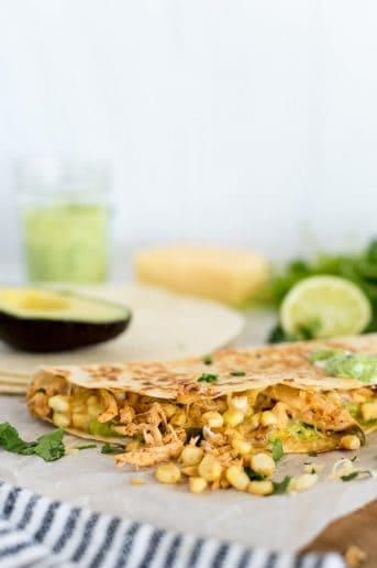 street corn quesadillas with avocado on a cutting board with lime