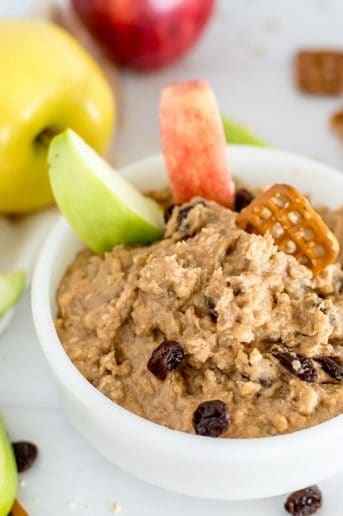 white bowl of oatmeal raisin cookie dough dip with apple slices