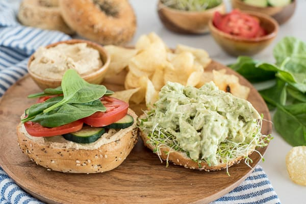open faced chicken with green sauce on a bagel with tomato and spinach
