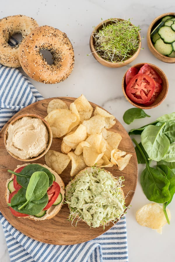open faced chicken with green sauce on a bagel with tomato and spinach and chips on the side