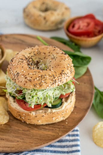 chicken with green sauce on a bagel with tomato and spinach