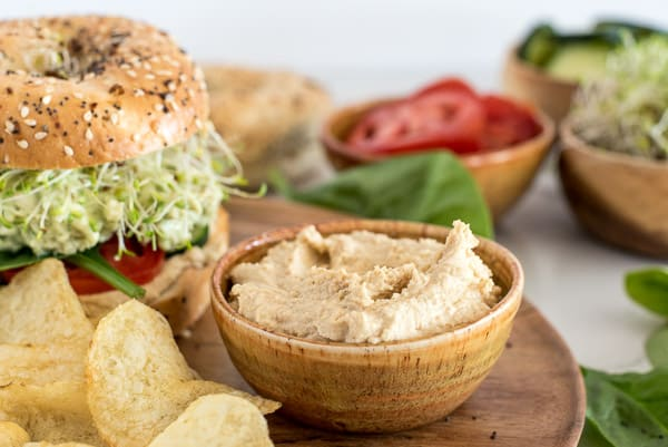 bowl of hummus next to a bagel sandwich