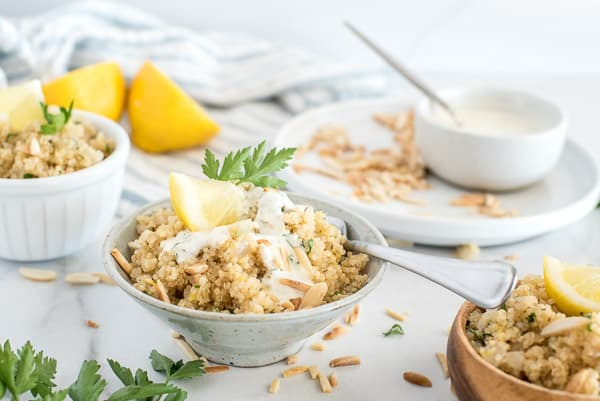white bowl with quinoa, lemon, and herbs with a spoon