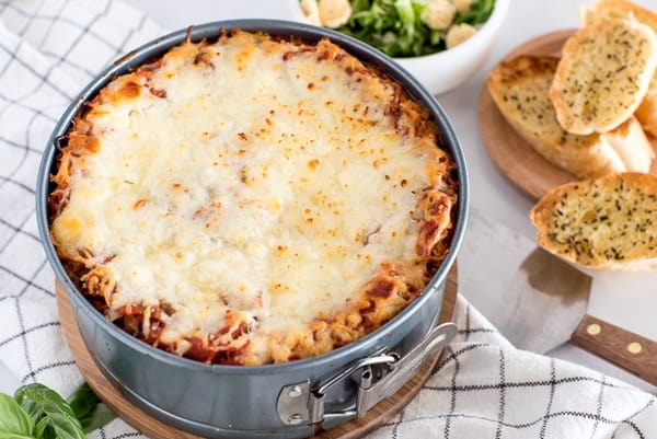 cheesy lasagna in a pan on top of a striped towel