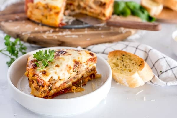 slice of lasagna on a white plate with a piece of garlic bread