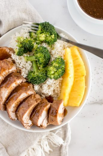 Pork tenderloin smothered with sauce and plated with broccoli, rice and pineapple